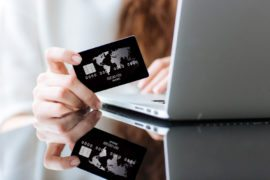 Closeup portrait of woman shopping online on laptop computer with credit card